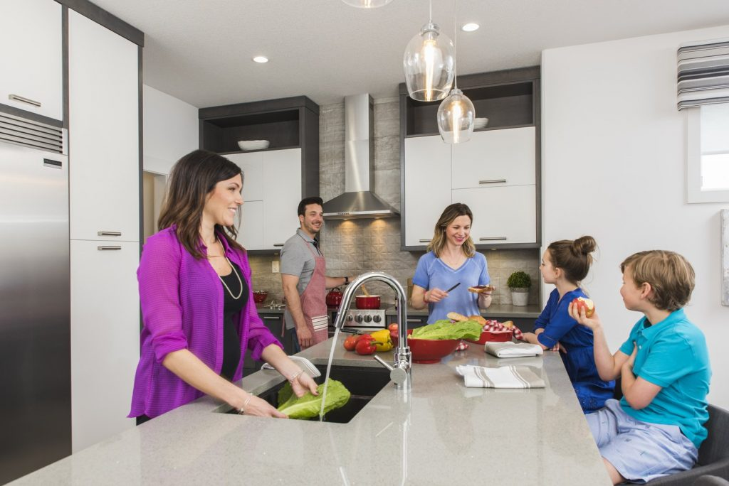 family cooking together in a bright modern kitchen