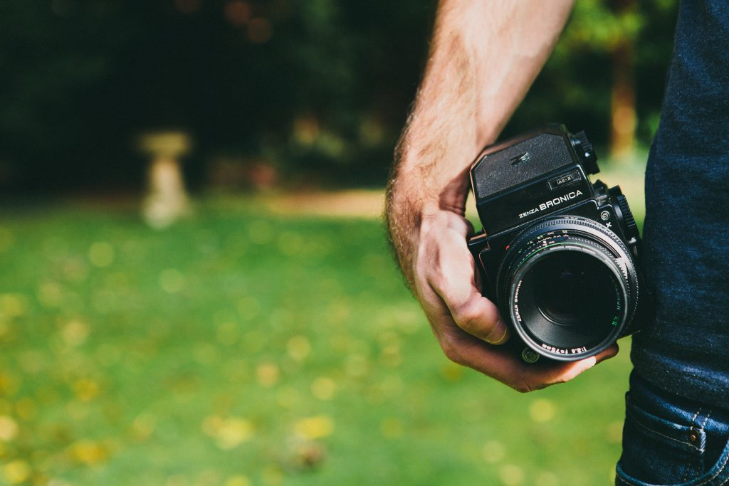 photographer holding a medium format camera on a yard