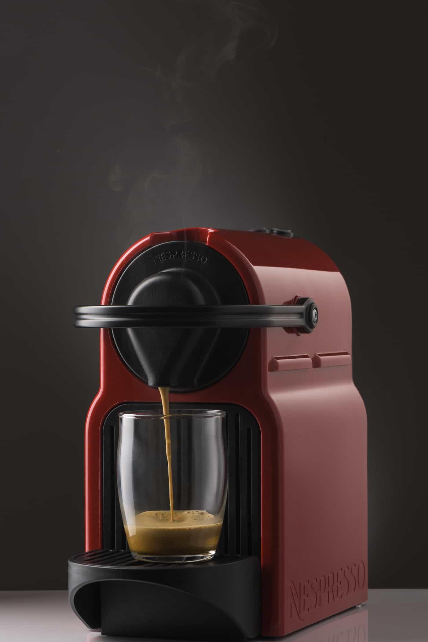 red nespresso machine pouring an espresso shot