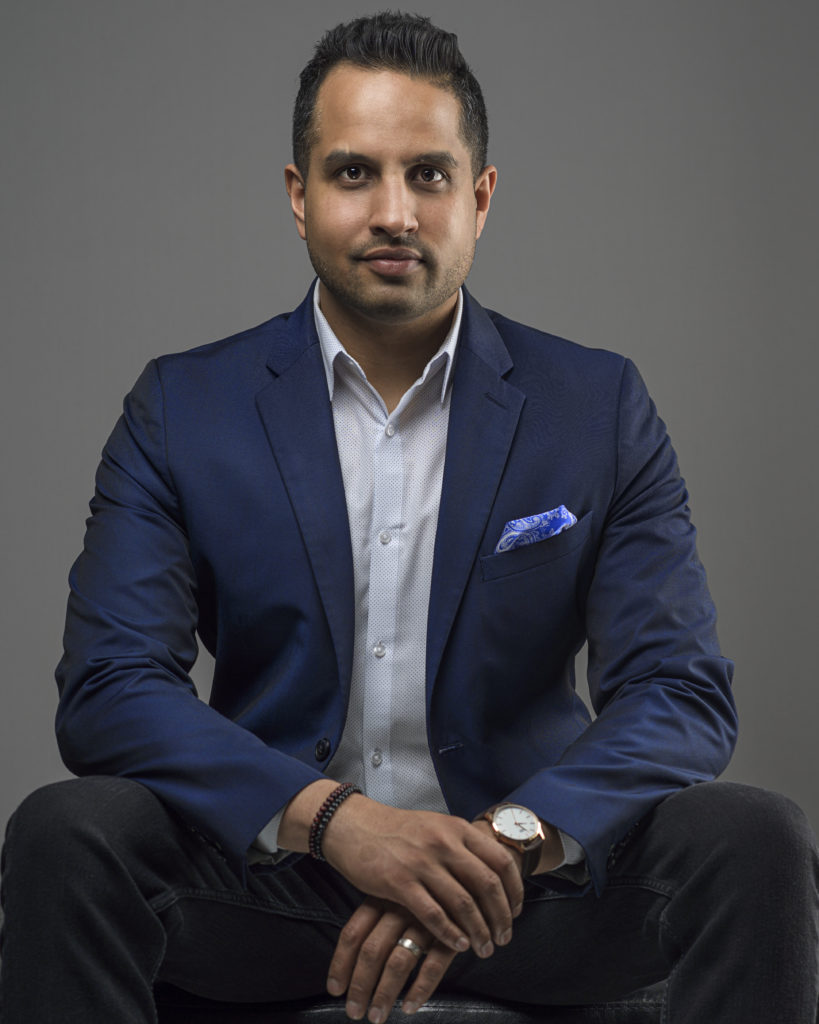 casual headshot with a blue suit and hands showing